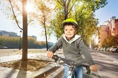 Embrome al muchacho en bici del montar a caballo del casco de seguridad en la trayectoria del ciclo Imagen de archivo