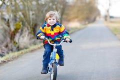 Embrome al muchacho en el casco de seguridad y la bici colorida del montar a caballo del impermeable, outd Imagen de archivo libre de regalías