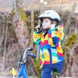 Embrome al muchacho en el casco de seguridad y la bici colorida del montar a caballo del impermeable, outd Imagen de archivo