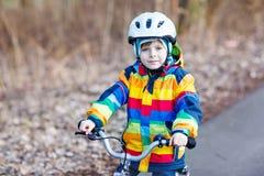 Embrome al muchacho en el casco de seguridad y la bici colorida del montar a caballo del impermeable, outd Imagenes de archivo