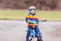 Embrome al muchacho en el casco de seguridad y la bici colorida del montar a caballo del impermeable, outd Fotografía de archivo