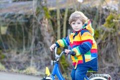 Embrome al muchacho en el casco de seguridad y la bici colorida del montar a caballo del impermeable, outd Imágenes de archivo libres de regalías