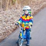 Embrome al muchacho en el casco de seguridad y la bici colorida del montar a caballo del impermeable, outd Foto de archivo libre de regalías