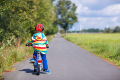 Embrome al muchacho en el casco que monta su primera bici, al aire libre Fotos de archivo