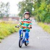 Embrome al muchacho en el casco que monta su primera bici, al aire libre Fotografía de archivo