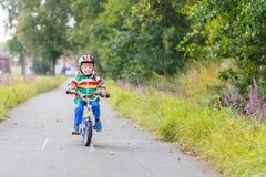 Embrome al muchacho en el casco que monta su primera bici, al aire libre Fotos de archivo libres de regalías