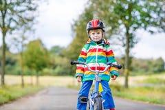 Embrome al muchacho en el casco que monta su primera bici, al aire libre Foto de archivo