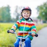 Embrome al muchacho en el casco que monta su primera bici, al aire libre Imágenes de archivo libres de regalías