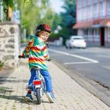 Embrome al muchacho en el casco que monta su primera bici, al aire libre Foto de archivo libre de regalías
