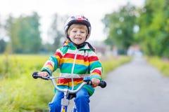 Embrome al muchacho en el casco que monta su primera bici, al aire libre Imagen de archivo libre de regalías