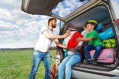 Embrome al muchacho que ayuda a su padre a cargar su bota del coche imagen de archivo libre de regalías