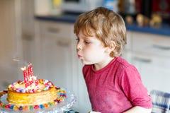 Embrome al muchacho que celebra su cumpleaños y que sopla velas en la torta Fotos de archivo libres de regalías
