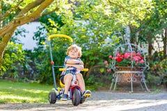 Embrome al muchacho que conduce el triciclo o la bicicleta en jardín Imagen de archivo libre de regalías