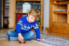 Embrome al muchacho que juega con el juguete de madera de la balanza en casa Fotos de archivo libres de regalías