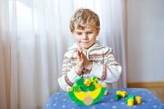 Embrome al muchacho que juega con el juguete de madera de la balanza en casa Foto de archivo