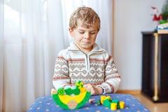 Embrome al muchacho que juega con el juguete de madera de la balanza en casa Fotografía de archivo