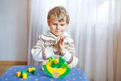 Embrome al muchacho que juega con el juguete de madera de la balanza en casa Imágenes de archivo libres de regalías