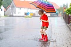 Embrome al muchacho que lleva las botas de lluvia rojas y que camina con el paraguas Imagenes de archivo