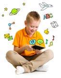 Embrome al muchacho que se sienta con la tableta y el aprendizaje o jugar Imagen de archivo libre de regalías