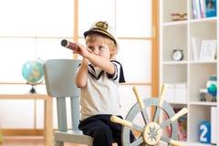 Embrome al muchacho vestido como juegos de un capitán o del marinero en silla como nave en su sitio El niño mira a través del tel imagen de archivo