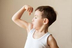 Embrome al niño del muchacho que muestra el entrenamiento de la fuerza del puño de los músculos Foto de archivo libre de regalías