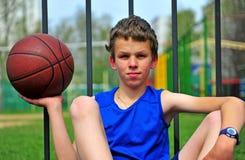 Embrome con un baloncesto en la corte del deporte Imagenes de archivo