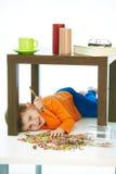 Embrome debajo de la tabla con la piruleta y los dulces sacuden derramado Imágenes de archivo libres de regalías