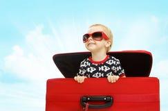Embrome dentro de la maleta, niño que mira hacia fuera al bebé feliz del equipaje del viaje fotografía de archivo