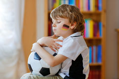 Embrome el fútbol o el partido de fútbol de observación del muchacho en la TV Imagenes de archivo