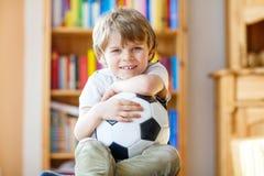 Embrome el fútbol o el partido de fútbol de observación del muchacho en la TV Fotografía de archivo