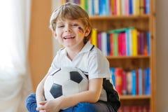 Embrome el fútbol o el partido de fútbol de observación del muchacho en la TV Imagen de archivo libre de regalías