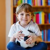 Embrome el fútbol o el partido de fútbol de observación del muchacho en la TV Fotos de archivo libres de regalías