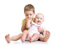 Embrome el muchacho y a su bebé de la hermana aislados en blanco Imagen de archivo libre de regalías
