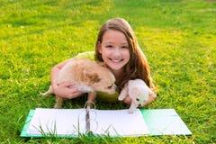 Embrome el perro de la muchacha y de perrito en la preparación que miente en césped Imagen de archivo libre de regalías