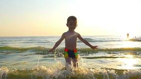 Embrome el salto en una playa del mar en la puesta del sol metrajes