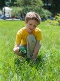 Embrome en el parque que mira la hierba con una lupa Muchacho lindo que hace experimentos al aire libre Imagen de archivo libre de regalías