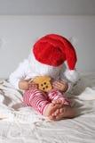 Embrome en el sombrero de Papá Noel que juega en el hogar de la cama, luz, nuevo Year& x27; concep de s Imagen de archivo libre de regalías