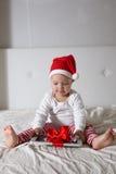 Embrome en el sombrero de Papá Noel que juega en el hogar de la cama, luz, nuevo Year& x27; concep de s Imágenes de archivo libres de regalías