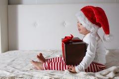 Embrome en el sombrero de Papá Noel que juega en el hogar de la cama, luz, nuevo Year& x27; concep de s Fotografía de archivo