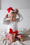 Embrome en el sombrero de Papá Noel que juega en el hogar de la cama, luz, nuevo Year& x27; concep de s Foto de archivo