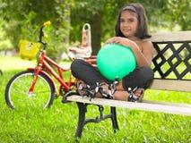 Embrome en un parque que se sienta en un banco Foto de archivo libre de regalías
