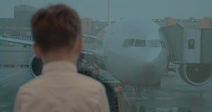 Embrome esperar en el aeropuerto y la mirada del avión a través de la ventana almacen de metraje de vídeo