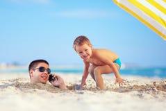 Embrome jugar alrededor de la cabeza del padre en la arena, hablando en el teléfono celular Fotos de archivo libres de regalías