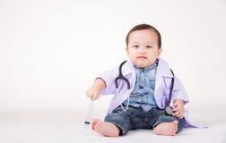 Embrome jugar a un doctor con el estetoscopio, jeringuilla, lleve el vestido blanco Imagen de archivo libre de regalías