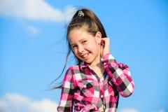 Embrome la camisa de moda a cuadros de la muchacha que plantea el fondo del cielo azul del día soleado Modelo de moda Girl Niño d imagen de archivo