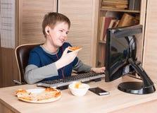 Embrome la consumición de la pizza y practicar surf en Internet o watshing el vídeo divertido Imagen de archivo libre de regalías
