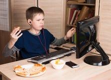 Embrome la consumición de la pizza y practicar surf en Internet o watshing el vídeo el picosegundo Imagen de archivo