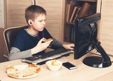 Embrome la consumición de la pizza y practicar surf en Internet o watshing el vídeo el picosegundo Imágenes de archivo libres de regalías
