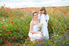 Embrome a la hija que abraza a su madre entre las flores rojas de la suma Foto de archivo
