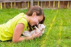 Embrome la mentira feliz del perro de la muchacha y de perrito en césped Imagenes de archivo